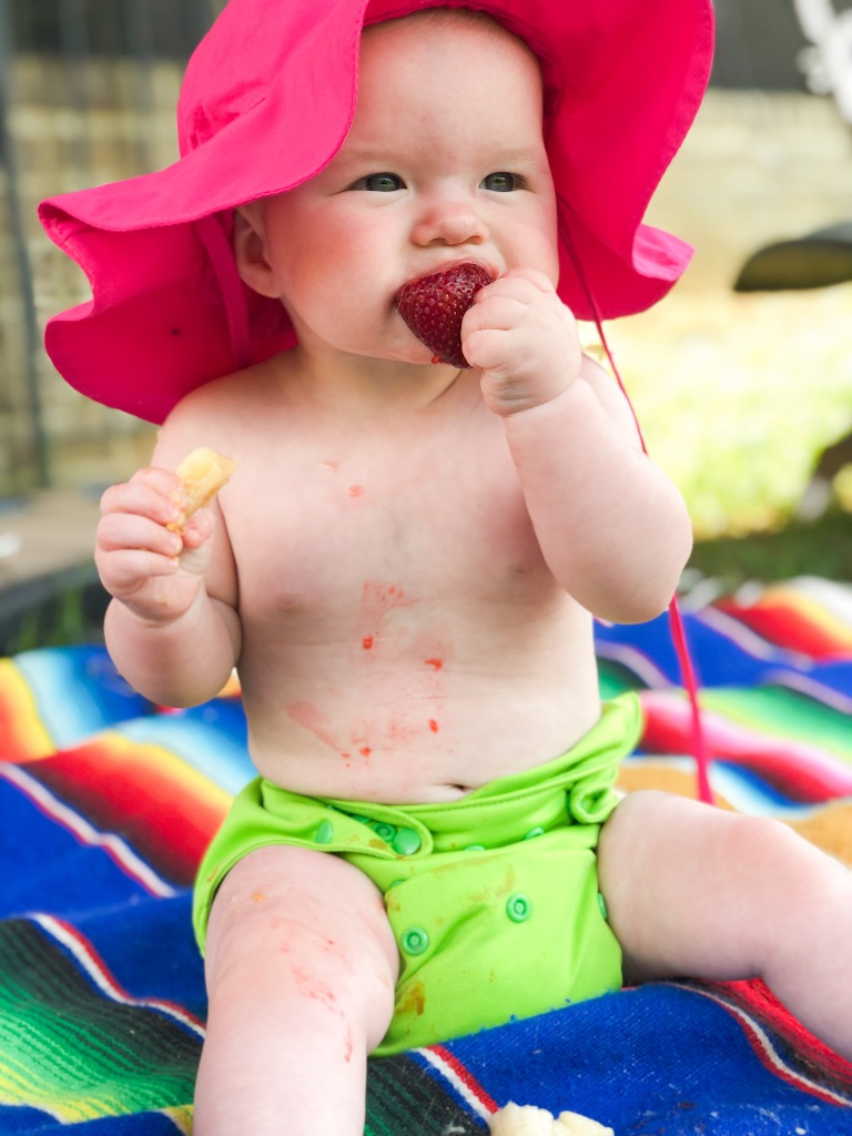 Baby in cloth diaper eating a strawberry and peach outdoors.