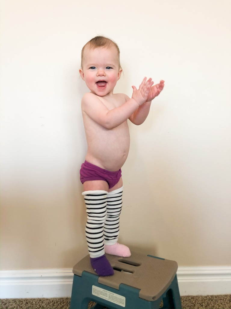 Baby standing on a step stool wearing tiny training pants and leg warmers.